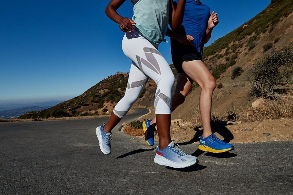 due runner che corrono su strada con scarpe hoka