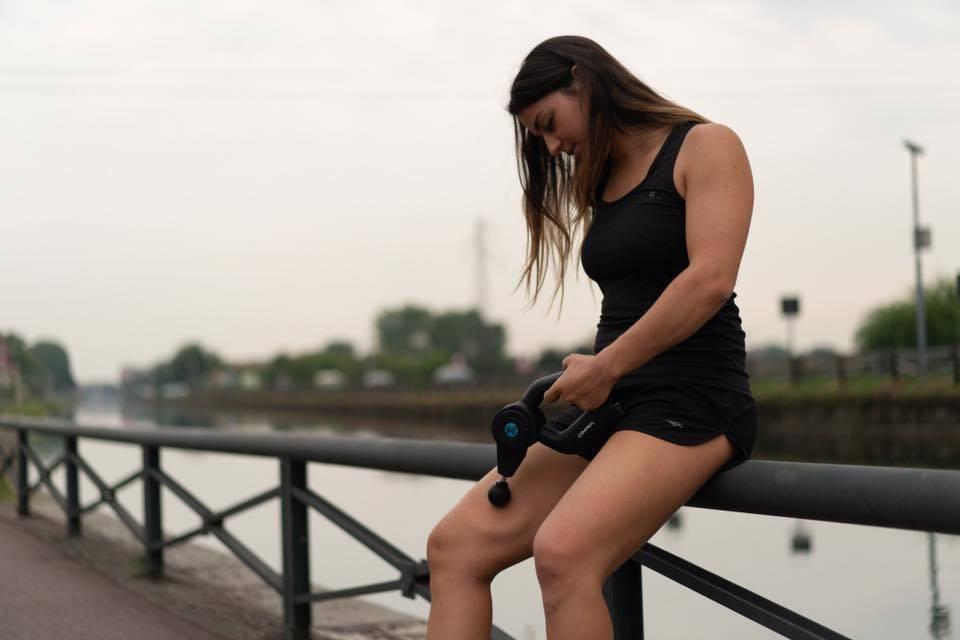 ragazza usa la pistola per massaggi modello Compex fixx 1.0