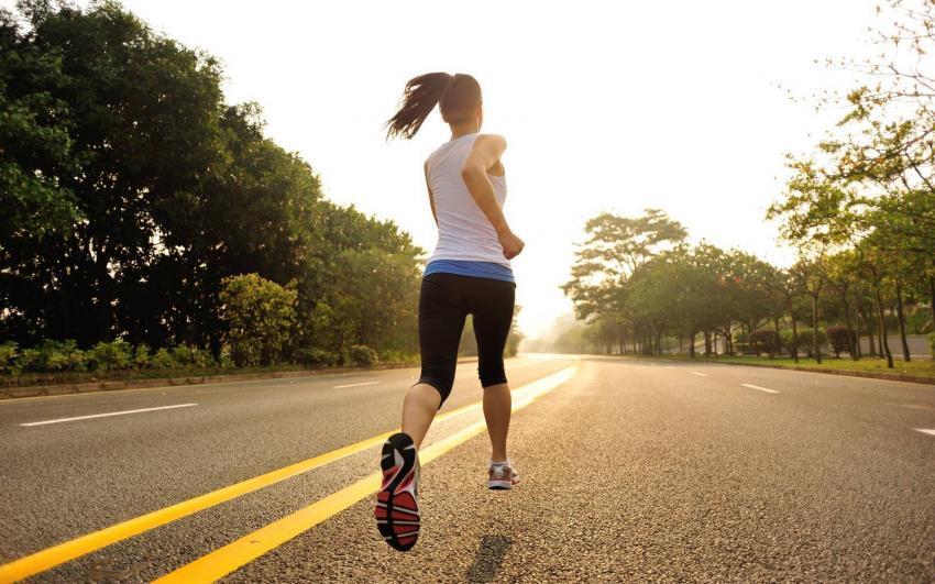 ragazza corre su strada asfaltata