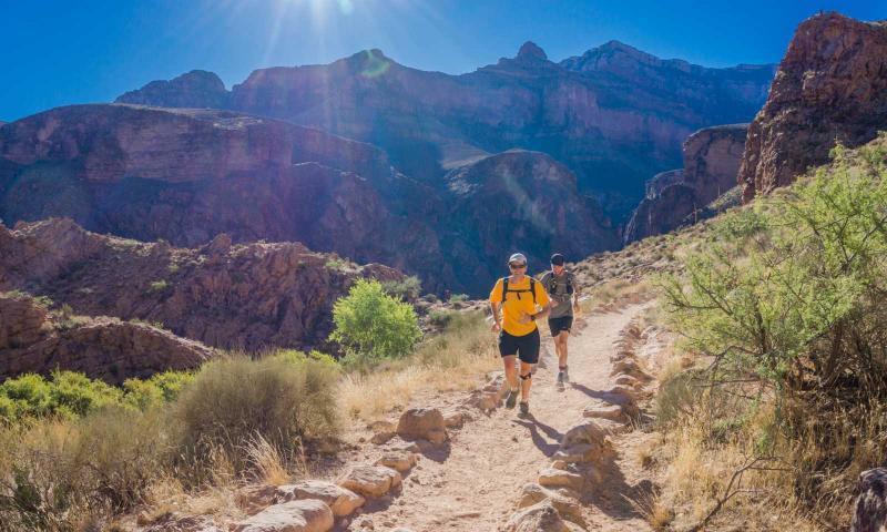 2 runner corrono su strada sterrata immersi nella natura