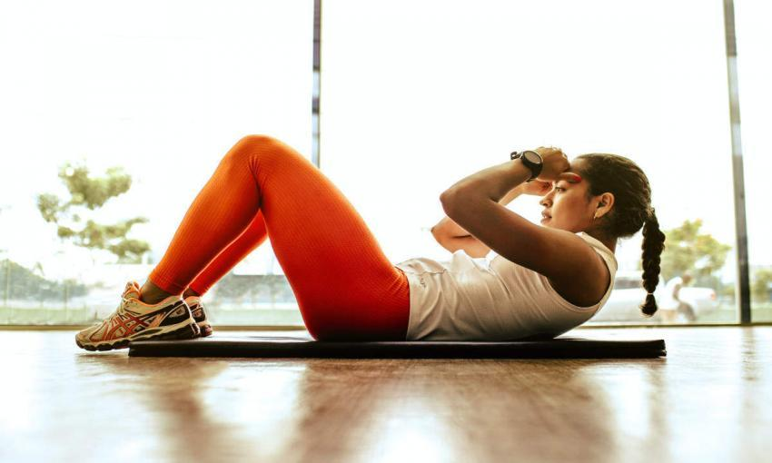 ragazza esegue addominali e esercizi funzionali per il running