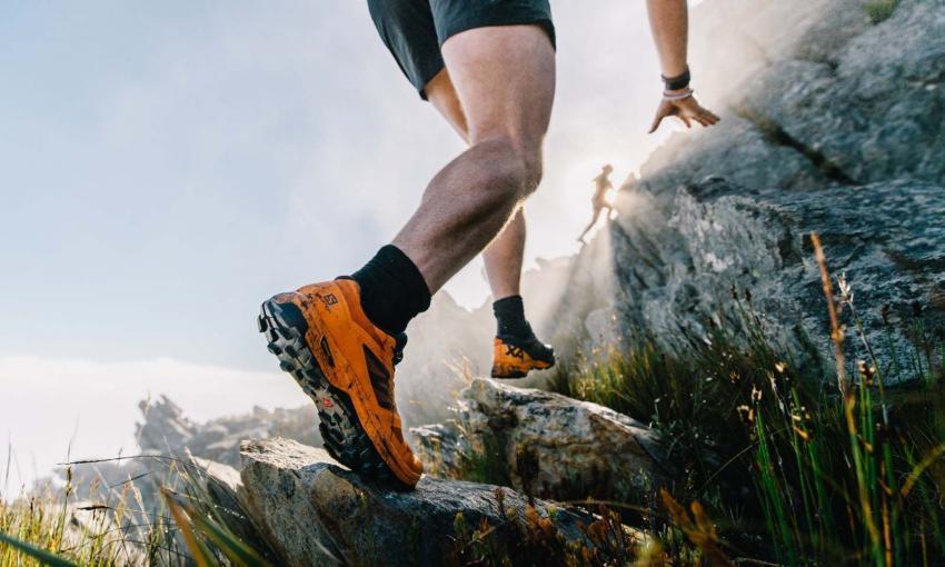 runner con scarpe salomon corre una gara trail running su terreno roccioso