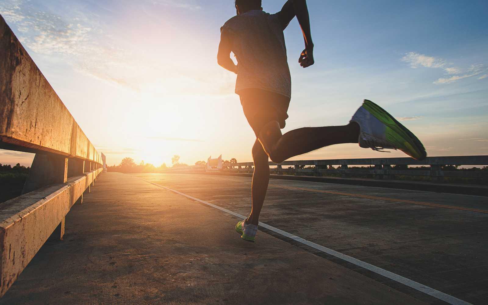 runner corre su strada all'alba