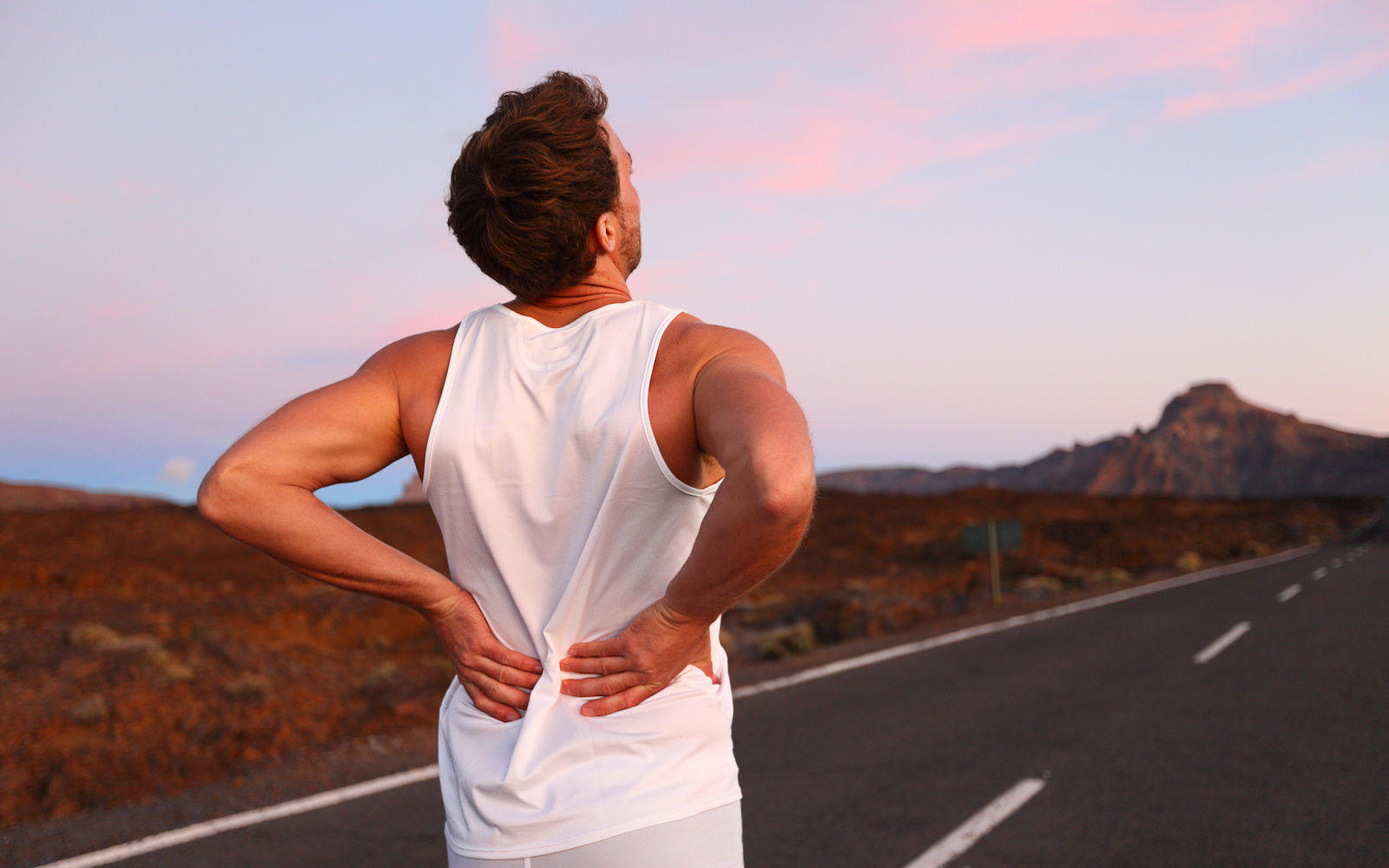 Back pain. Athletic running man with injury in sportswear rubbing touching lower back muscles standing on road outside at night.