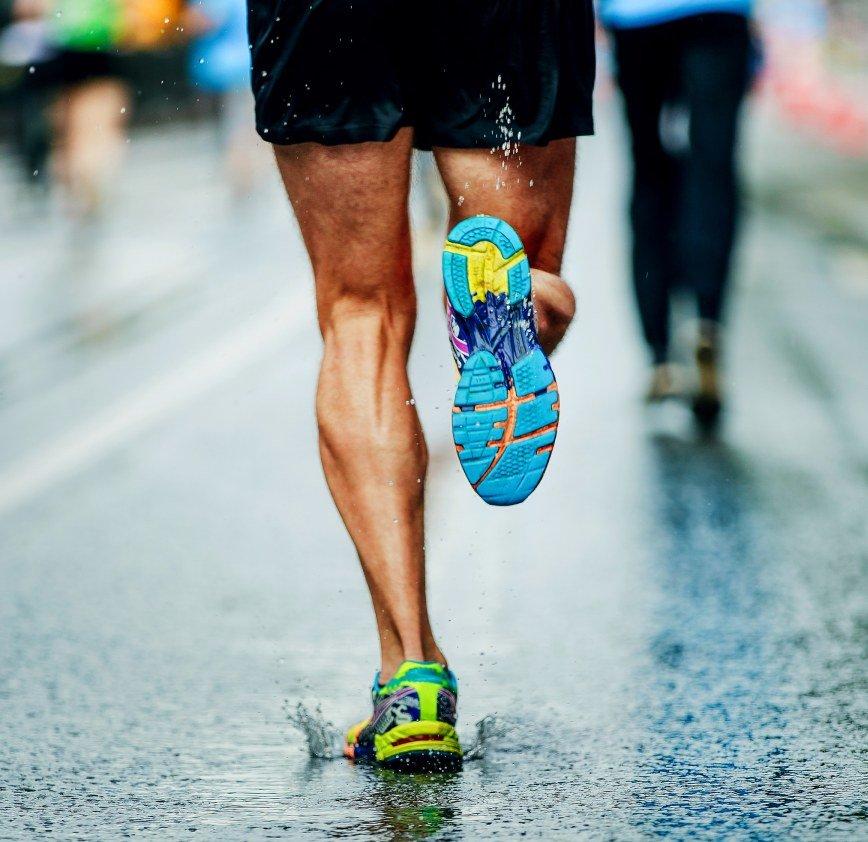 runner corre con scarpe running sotto la pioggia