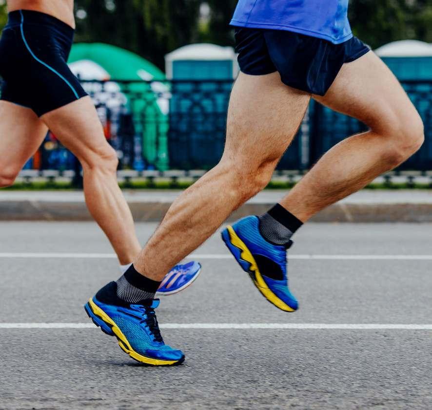 runner corrono con scarpe da corsa blu su asfalto
