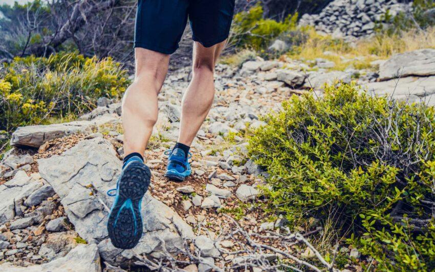 runner con scarpe da trail corre su sterrato in montagna