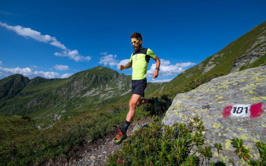 runner con t-shirt tecnica, pantaloncini e scarpe da trail corre in montagna
