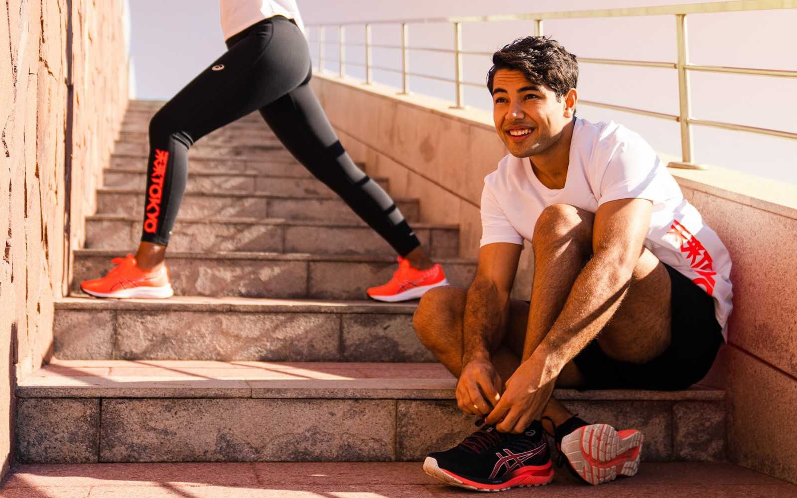 2 ragazzi sulle scarpe vestiti con abbigliamento tecnico da running asics collezione tokyo sunrise red