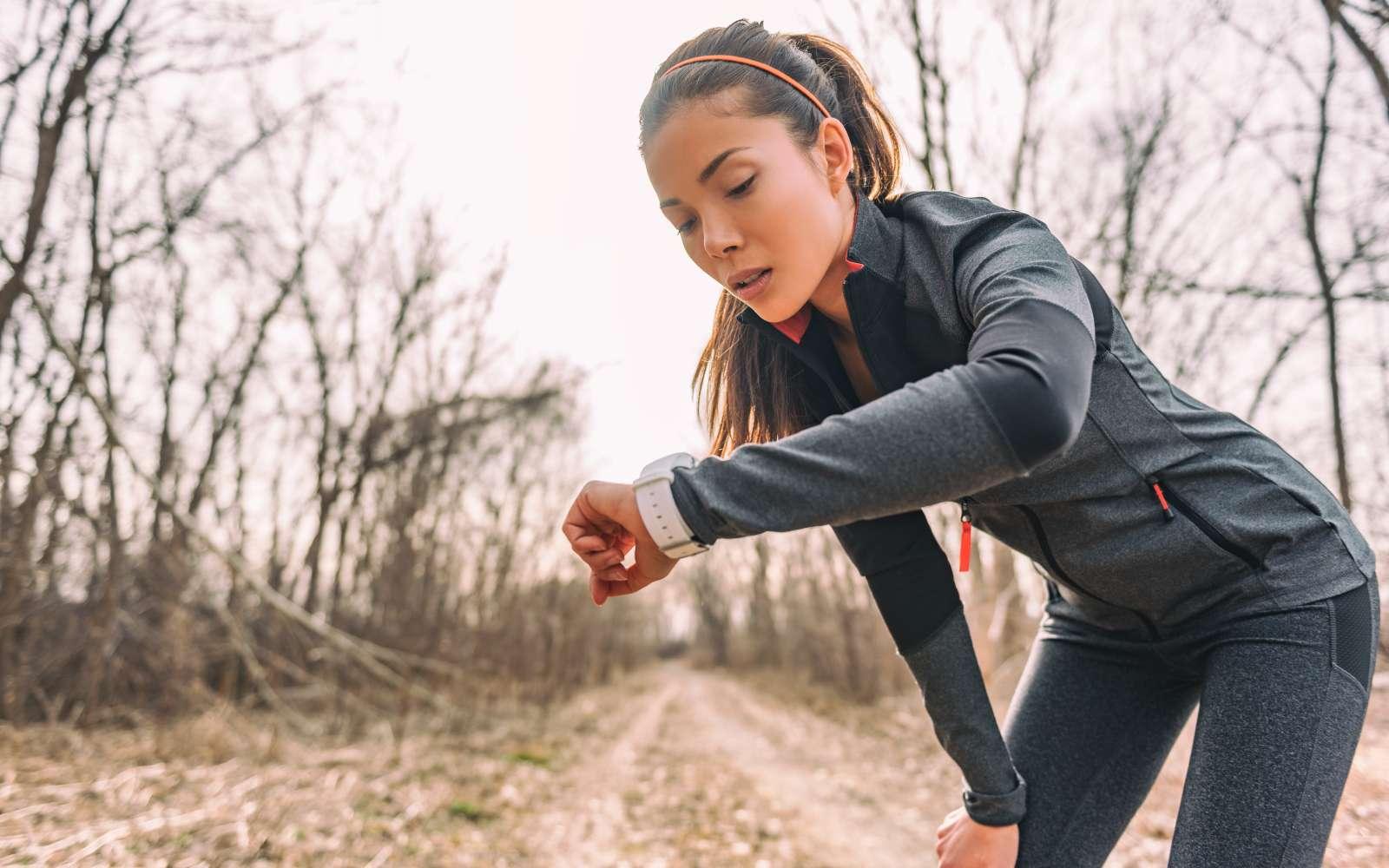 ragazza vestita con abbigliamento tecnico grigio da running guarda l'orologio tra un esercizio e l'altro