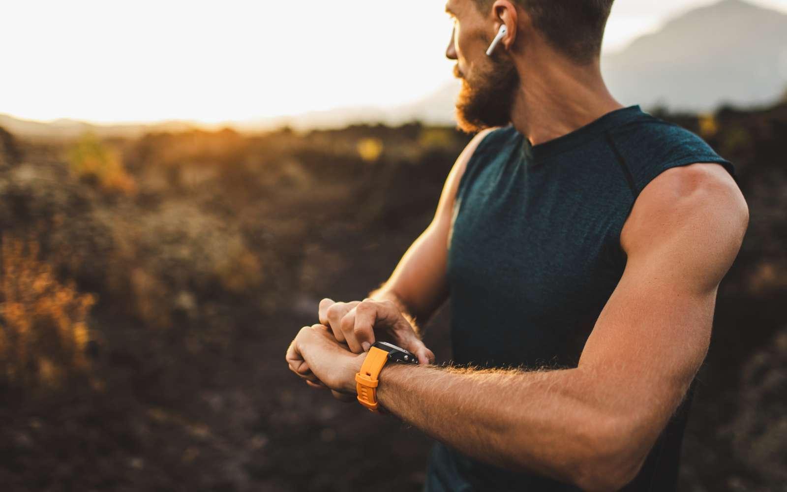 runner con canotta e cuffie senza filo controlla la frequenza cardiaca sull'orologio